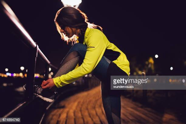 woman runner tying her shoelaces on a pier at night - self improvement stock pictures, royalty-free photos & images
