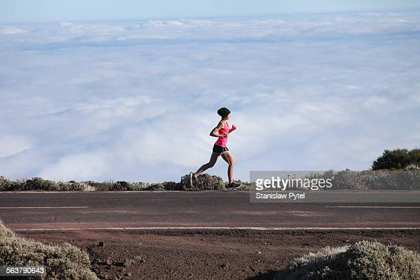 Woman running above clouds in pink shirt