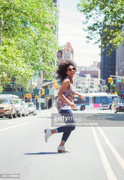 woman running across city street - street style new york stock pictures, royalty-free photos & images