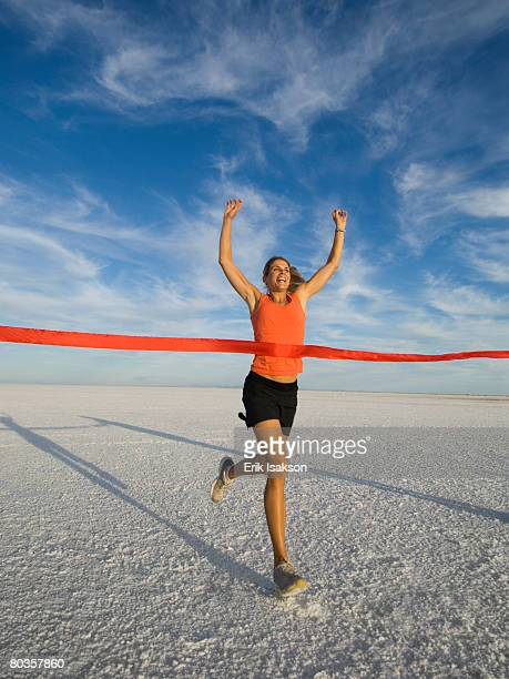 Woman running across finish line, Utah, United States
