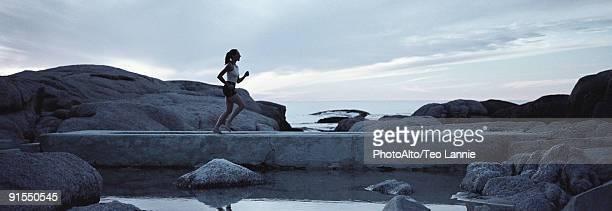woman running across footbridge near seashore in early morning - pantaloncini grigi foto e immagini stock