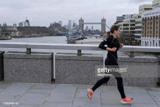 Woman running across London Bridge looking towards Tower Bridge as the national coronavirus lockdown three continues on 28th January 2021 in London,...