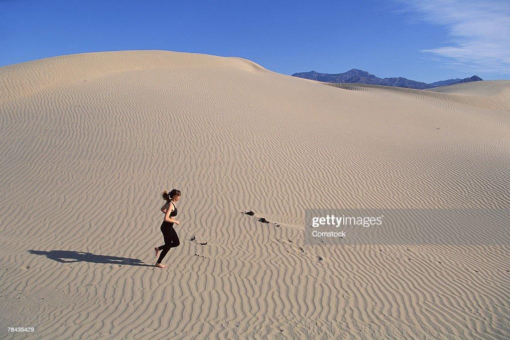Woman running across sand dunes , Death Valley , California : Stockfoto