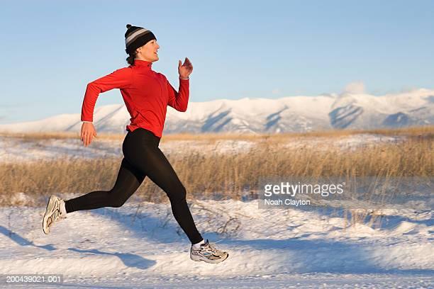 Woman running across snow, side view, winter