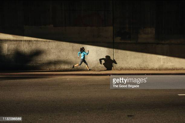 woman running against wall on city street - rennen stockfoto's en -beelden