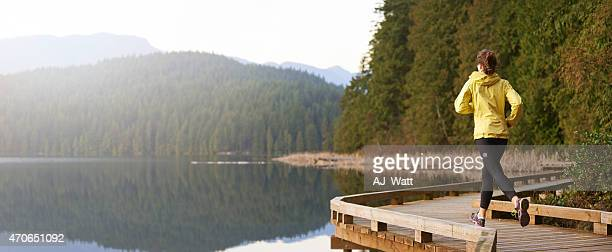 woman running along a wooden lakeside path - individual event stock pictures, royalty-free photos & images