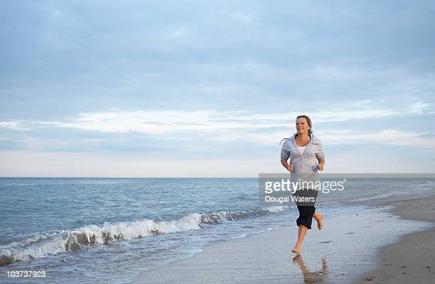 Woman running along beach.