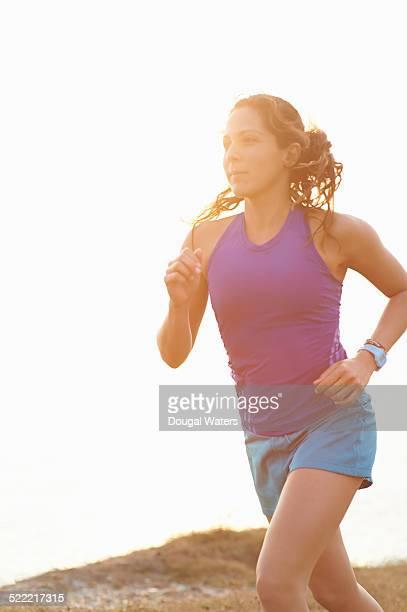 Woman running along coastline at sunset.