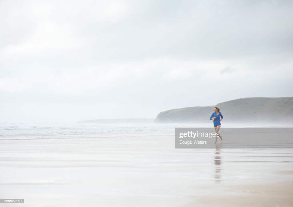 Woman running along misty beach. : Stock Photo