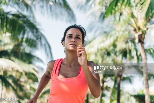 woman running along palm tree beach