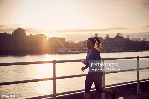 a woman running alongside the river thames in london - dusk stock pictures, royalty-free photos & images
