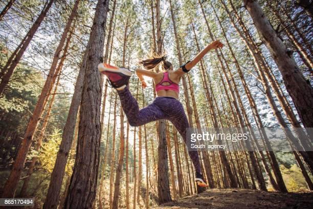 Femme de courir et sauter dans une forêt