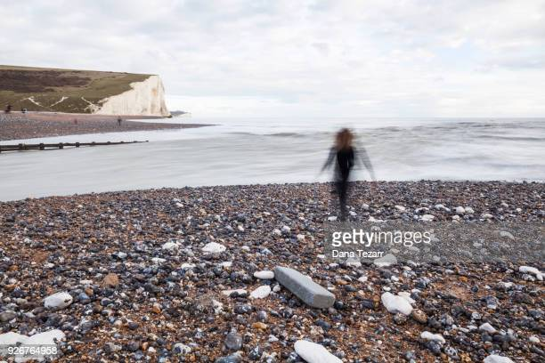 Woman running at beach where the river Cuckmere floats into the sea with white cliffs in the background