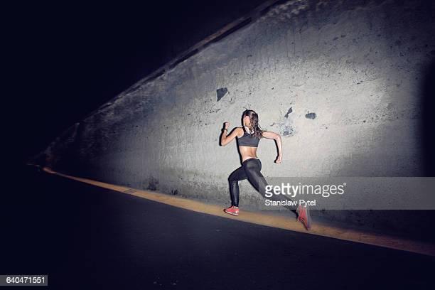 woman running at night against grey wall - corredor caraterística de construção imagens e fotografias de stock