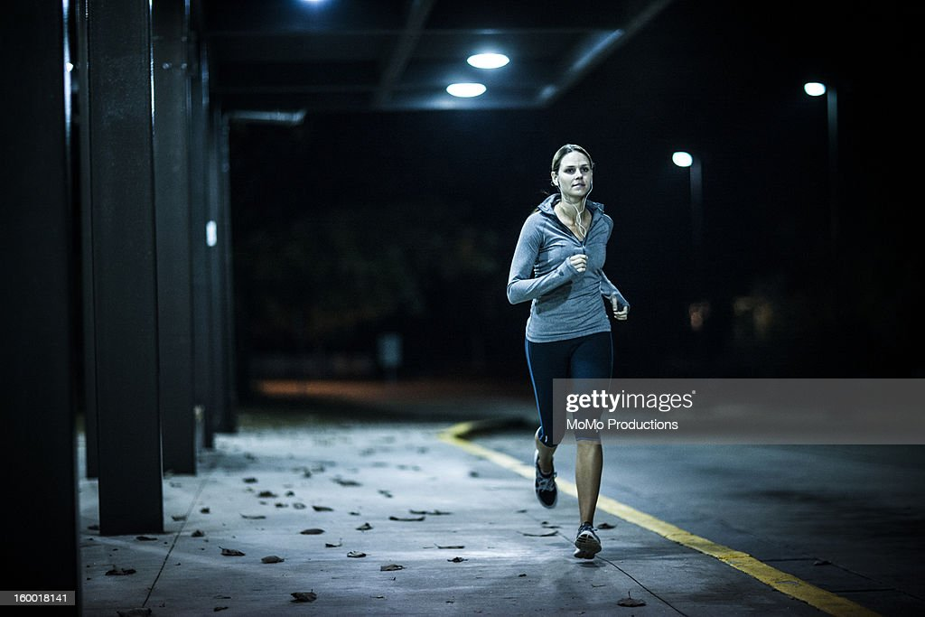 woman running at nighttime : Stock Photo