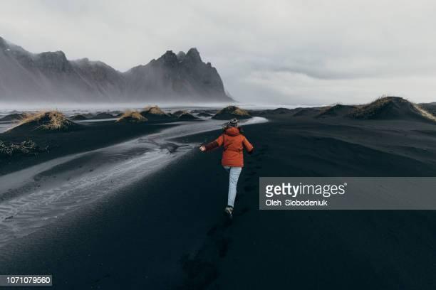 Woman running away near  Vestrahorn mountains near the sea