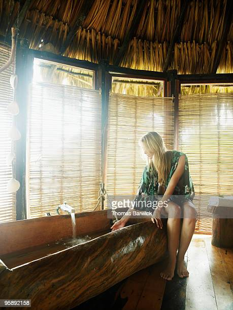woman running bath in eco lodge bungalow - yucatan peninsula stock pictures, royalty-free photos & images