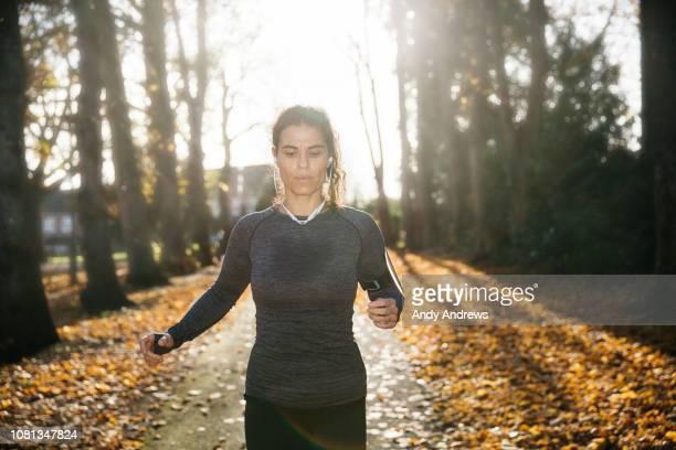 Woman running down a leafy footpath