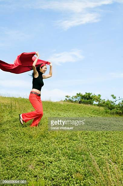 woman running down hill holding cape over head - cape stock pictures, royalty-free photos & images