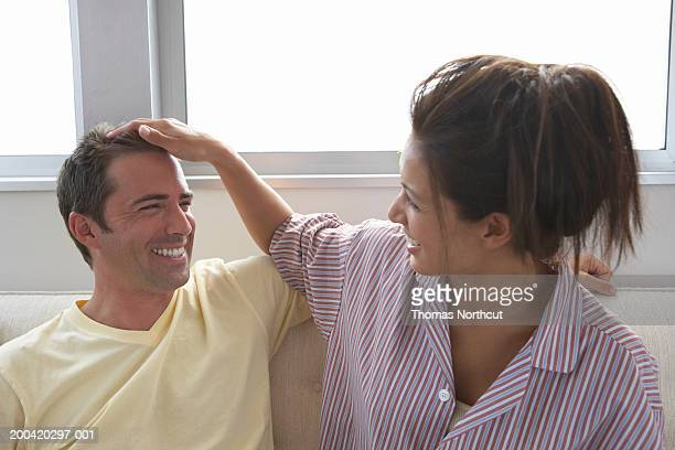 woman running fingers through man's hair on sofa, laughing - 30 39 years stock photos and pictures