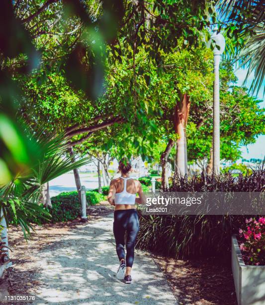woman running for exercise along a shaded path in an urban city, foliage - city_(florida) stock pictures, royalty-free photos & images