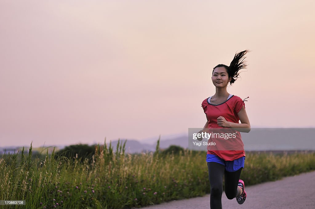Woman running for exercise at sunset. : Stock Photo