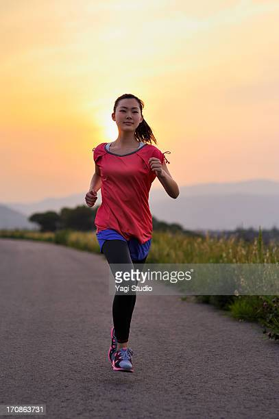 Woman running for exercise at sunset.