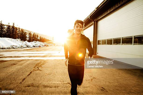 Woman running hard at sunset.