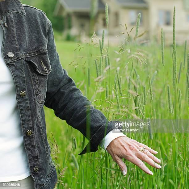 Woman running her hands through field grass