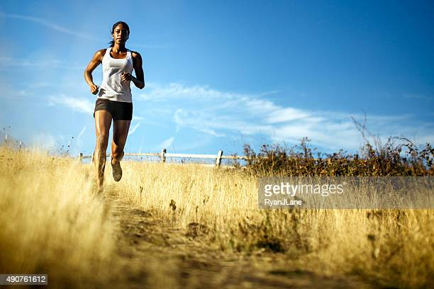 woman running in beautiful nature setting - cross country running stock pictures, royalty-free photos & images