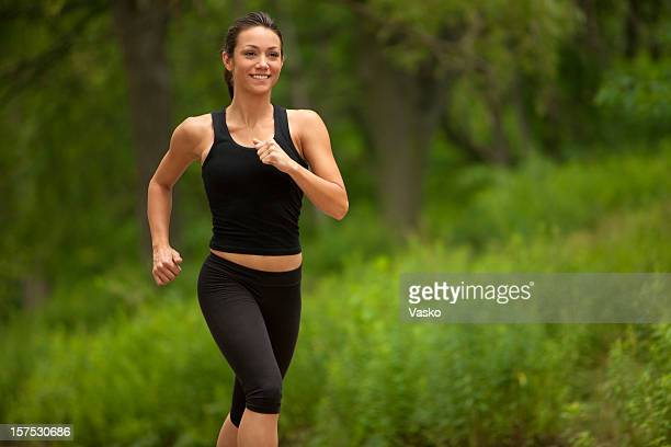 A woman running in black workout outfit