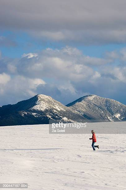 Woman running in empty snow covered landscape, side view