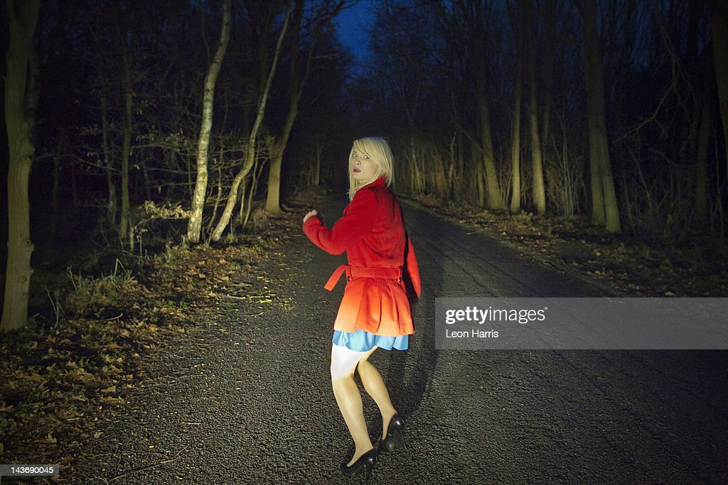 Woman running in fear in woods at night : Stock Photo
