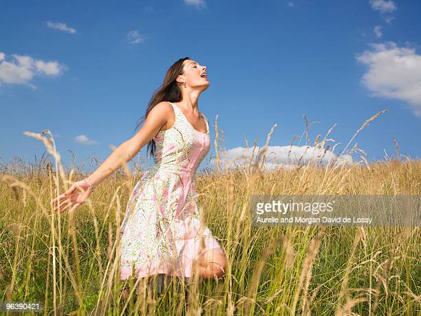 woman running in field of high grasses - aquitaine stock photos and pictures
