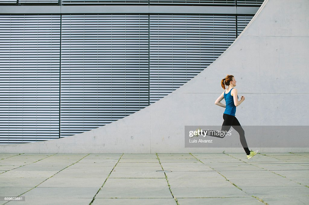 Woman running in front of a building : Stock-Foto