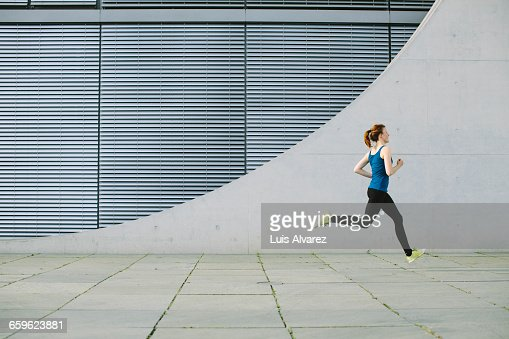 Woman running in front of a building