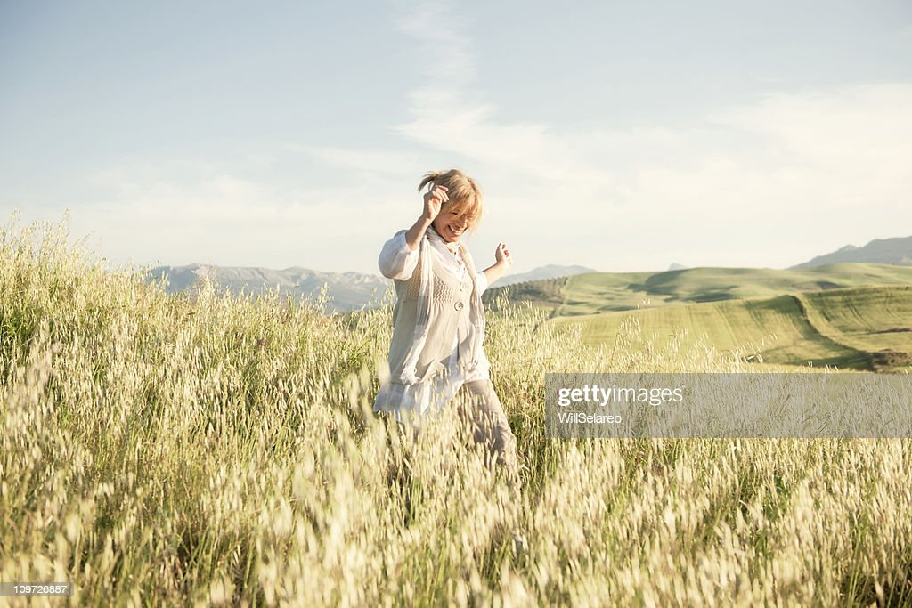 Woman running in grassy field : Stockfoto