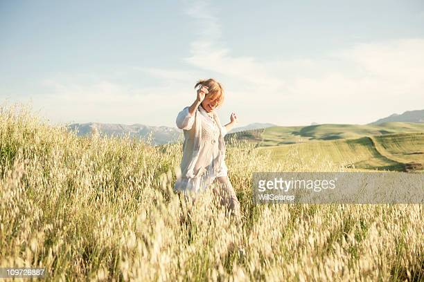 woman running in grassy field - mature women stock pictures, royalty-free photos & images