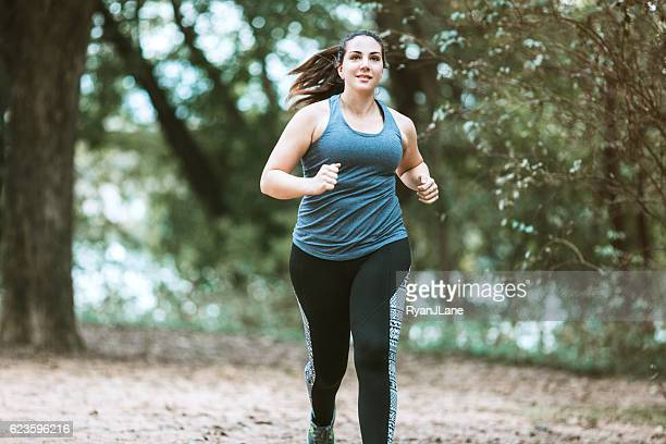 woman running in park - chubby stock photos and pictures
