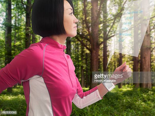 Woman running in park with smartwatch