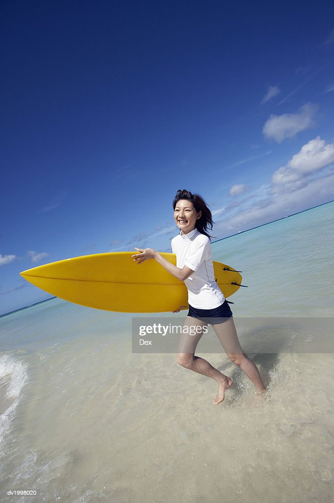 Woman Running in the Sea With a Surfboard : Stock Photo