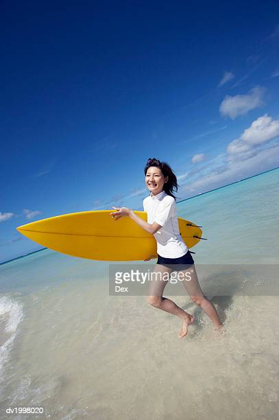 Woman Running in the Sea With a Surfboard