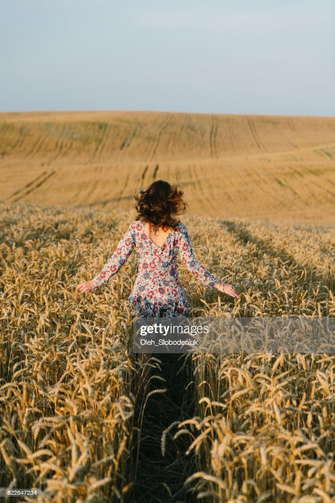 Woman running in the wheat field : Stock Photo