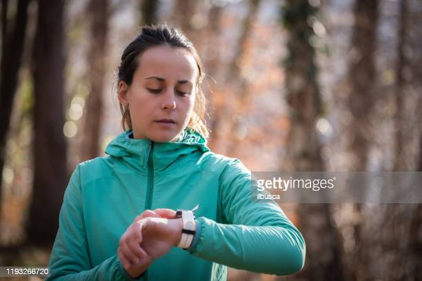woman running in the woods checking smartwatch - ilbusca foto e immagini stock