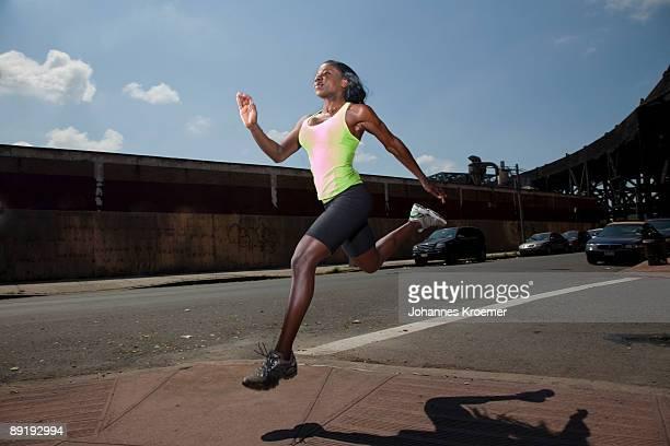 Woman running in urban setting, in motion