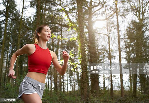 woman running in woodland. - running shorts stock pictures, royalty-free photos & images