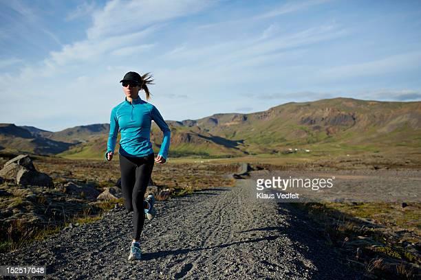 Woman running mountain trail