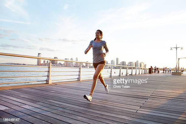 Woman running on a pier in front of city skyline