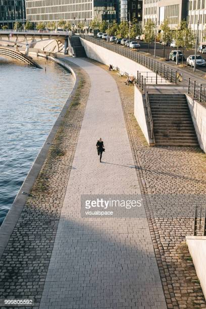 Woman running on a sunny evening by the river.