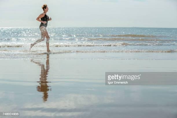 Woman running on beach, Folkestone, UK